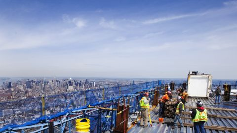 Ironworkers walk around the steel decking on the 100th story of the building on April 12, 2012.