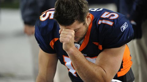 """Tebow prays during the final minute of a game in November 2011. The pose, which often came after touchdowns, came to be known as """"Tebowing."""""""