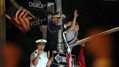 Servicemen cheer from a lamp post as thousands of people gather at Ground Zero in New York City.