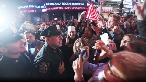 Crowds celebrate with NYPD officers in New York's Times Square early on May 2, 2011, after the death of Osama bin Laden.