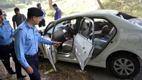 Pakistani police officials examine the bullet-riddled car of slain government prosecutor Chaudhry Zulfiqar after an attack by gunmen in Islamabad on May 3, 2013.