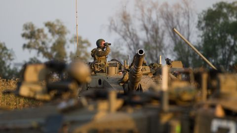 An Israeli soldier looks at his binoculars from the top of his Merkava tank during a drill near the border with Syria at the Israeli-annexed Golan Heights on May 6, 2013.