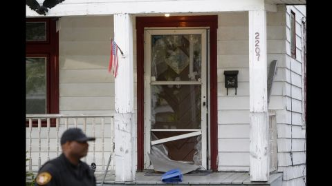 A police officer stands in front of the broken front door of the house where the kidnapped women escaped in Cleveland, Ohio, on May 7.