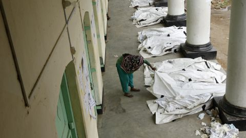 A woman attempts to identify one of the bodies kept in a schoolyard on May 7.
