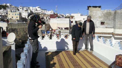 Bourdain looks at a Moroccan rug with the owner of Boutique Majid, Abedelmajid Rais El Fenni.