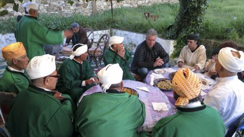 Bourdain shares a meal with Bachir Attar and the Master Musicians of Jajouka at Attar's home in the Moroccan village of Jajouka.