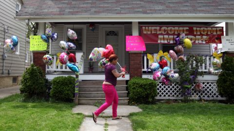A relative of DeJesus brings balloons to the home of Amanda Berry's sister in Cleveland on May 7.
