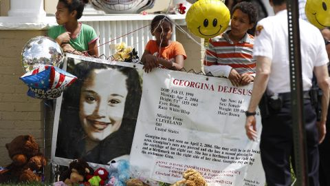 Children hold a sign and balloons in the yard of Gina DeJesus' family home in Cleveland on May 7.