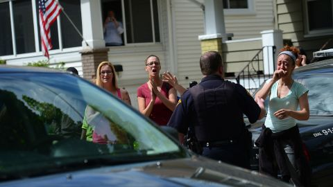 Friends and neighbors cheer as a car carrying Amanda Berry arrives at her sister's house in Cleveland on May 8.