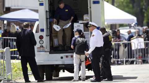 FBI agents and other law enforcement officers stand outside suspect Ariel Castro's home in Cleveland on May 9. Castro, a former school bus driver, has been accused of holding three women captive for a decade in his house. He has also been charged with rape.