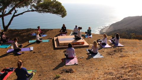 The day begins with a morning yoga session outside.