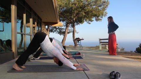 A smaller yoga class practices downward-facing dog ...