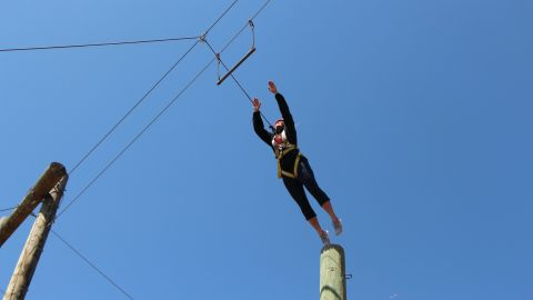 """Campers participate in the """"leap of faith,"""" springing from a 35-foot pole onto a trapeze."""