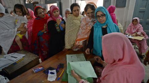 Voters in Rawalpindi gather around an election presiding officer to cast their ballots on May 11, 2013.