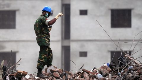 A Bangladeshi Army official gestures as he guides an excavator operator to removes debris as they continue the second phase of the rescue operation using heavy equipment after an eight-storey building collapsed in Savar, on the outskirts of Dhaka, on May 11, 2013. Bangladeshi doctors treating a 'miracle' survivor pulled from ruins of a collapsed building after 17 days said that she was doing 'great' and had been reunited with her family. Reshma, 18, a seamstress dug out from the rubble of the garment factory complex, 'never gave up hope' she would be rescued from the ruins of one of the world's worst industrial disasters, army doctor Fakrul Islam told AFP. AFP PHOTO/Munir uz ZAMAN (Photo credit should read MUNIR UZ ZAMAN/AFP/Getty Images)