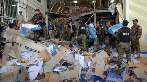 Cambodian soldiers move debris after the collapse. Shoes made by the Japanese sports apparel company Asics were in evidence at the factory.