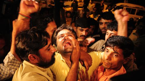 Members of the Tehreek-e-Insaf party mourn the death of Zahra Shahid Hussain, vice president of the party, outside a hospital in Karachi, Pakistan, on Saturday, May 18. Hussain had alleged vote-rigging in the May 11 elections.