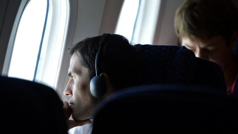 A passenger on United Airlines Flight 1 looks out one of the Dreamliner's oversized windows. The use of composite materials to build the airplane made larger window cutouts possible.