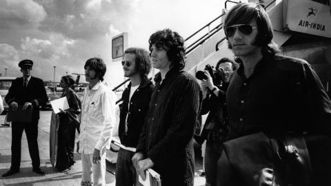 """From left, Densmore, Krieger, Morrison and Manzarek arrive at the London Airport in 1968. Their third studio album, """"Waiting for the Sun,"""" was released that year."""