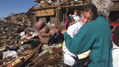 Nan Goines, right, hugs her granddaughter Ashley Thomas, on May 5, 1999, in front of the remains of her home in Midwest City, Oklahoma.