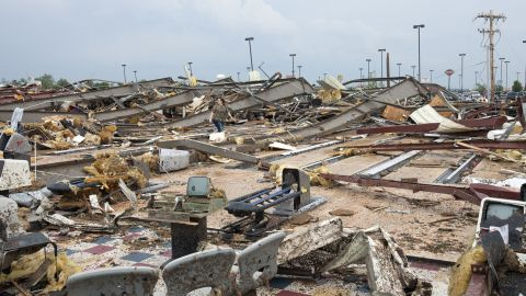 A woman walks through debris in Moore on May 20.