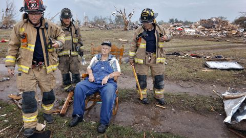 Oklahoma City firefighters check on Gene Tripp on May 20 as he sits in his rocking chair where his home once stood.