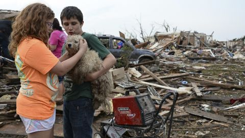 Abby Madi, left, and Peterson Zatterlee comfort Zatterlee's dog, Rippy, on Monday, May 20, in Moore.