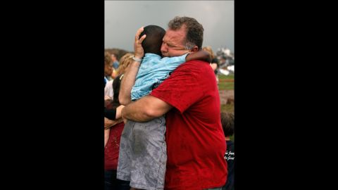 """Jim Routon hugs his neighbor, 7-year-old Hezekiah, after the tornado strikes on May 20. An earlier version of this caption incorrectly stated that Routon was Hezekiah's teacher. <a href=""""http://outfront.blogs.cnn.com/2013/05/21/neighbors-comfort-boy-in-tornado-aftermath/"""">See an interview with the pair.</a><strong> </strong>"""