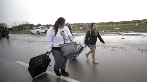 Bonnie Lolofie, left, and Ashley Do carry belongings from their apartment, which has no power, on May 21.