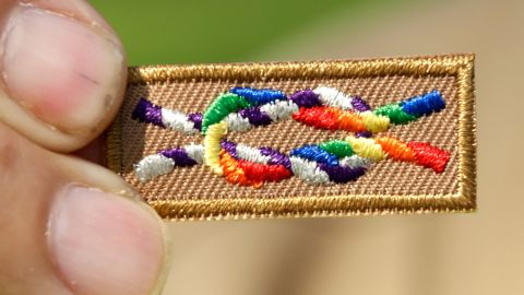 A member of Scouts for Equality holds an unofficial knot patch incorportating the colors of the rainbow, a symbol for gay rights.