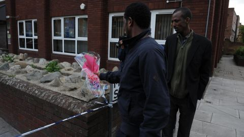 Men place flowers near the scene on John Wilson Street.