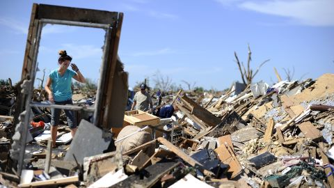 A woman searches for belongings at a home on May 22 in Moore.