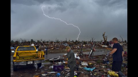 Lightning strikes during a thunderstorm as people search for items that can be saved from their devastated home on May 23.