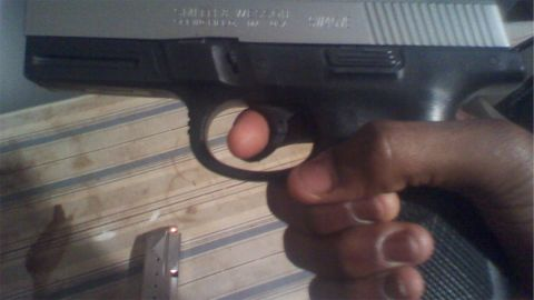 A person holds a gun in this image taken from Martin's cell phone.