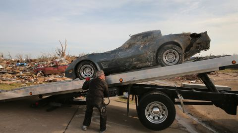 Mike Hitch loads a salvaged Corvette pulled from the rubble onto a tow truck in Moore on May 25.