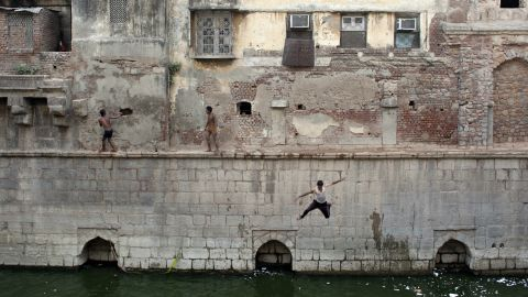 Indian youth jump from a wall into the Nizamuddin Baoli on a hot day in New Delhi, India, on May 28.