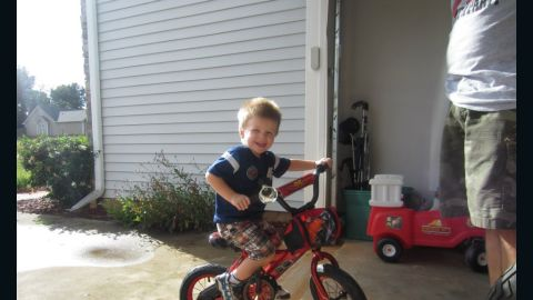 """August 2011: Tripp Halstead rides his new bike outside his home in Winder, Georgia. The bike, a gift from Tripp's grandfather, was inspired by Lightning McQueen from the movie """"Cars,"""" Tripp's favorite movie character."""