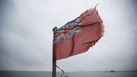 A red ensign flag flies on a ship at the location of the sinking of the Mary Rose which is marked by a yellow buoy.