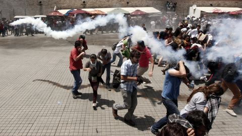 A crowd scatters during clashes on May 31, as one demonstrator throws back the tear gas canister that was launched by riot police.
