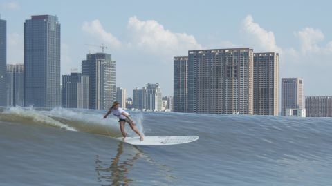 """Each year, international surfers compete on Qiantang River, riding the """"Silver Dragon"""" wave, which flows through the city of Hangzhou."""