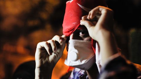 A protester covers his face on June 3 near Erdogan's office in Istanbul.