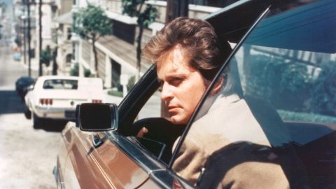 """Douglas peers out of the window of a car as Inspector Steve Keller on """"Streets of San Francisco."""""""