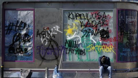 A tired protester rests in front of the graffiti-sprayed wall of an information booth at Taksim Square in central Istanbul on June 3.
