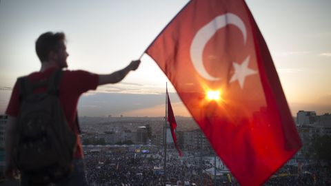 A protester waves the Turkish flag from a rooftop at Taksim Square on June 3 as large crowds continue to demonstrate below.
