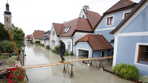 A women crosses a makeshift bridge over flooded streets in Unterloiben, Austria, on Tuesday, June 4.