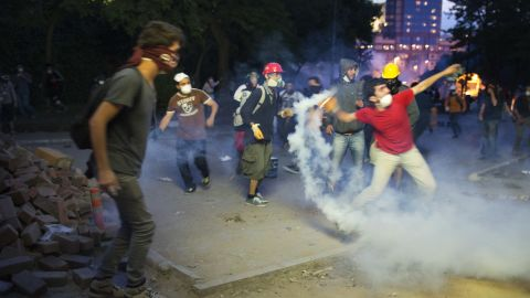 Protesters throw riot police's tear gas back at them in Istanbul on June 3.