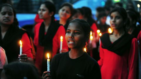 Members of India's 'Red Brigade' take part in a candlelight protest in Lucknow on May 7, 2013.
