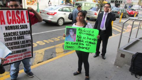 """What happened to 12 young people who were forced at gunpoint into a van in Mexico City's popular Zona Rosa entertainment district on May 26? <a href=""""http://www.cnn.com/2013/06/04/world/americas/mexico-missing-mystery/index.html?iref=allsearch"""">The mystery has gripped nation</a>. Penelope Ramirez is a cousin of Jerzy Ortiz Ponce, who is one of the 12 missing people. She holds a sign with his picture during a gathering of family members in the Tepito area of Mexico City on May 31."""