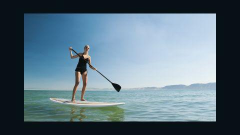 USA, Utah, Garden City, young woman standing on paddleboard