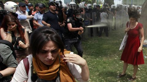 A riot police officer uses tear gas as people protest the destruction of a park for a pedestrian project in Istanbul's Taksim Square on May 28, 2013. The woman in red became the face of the protests.